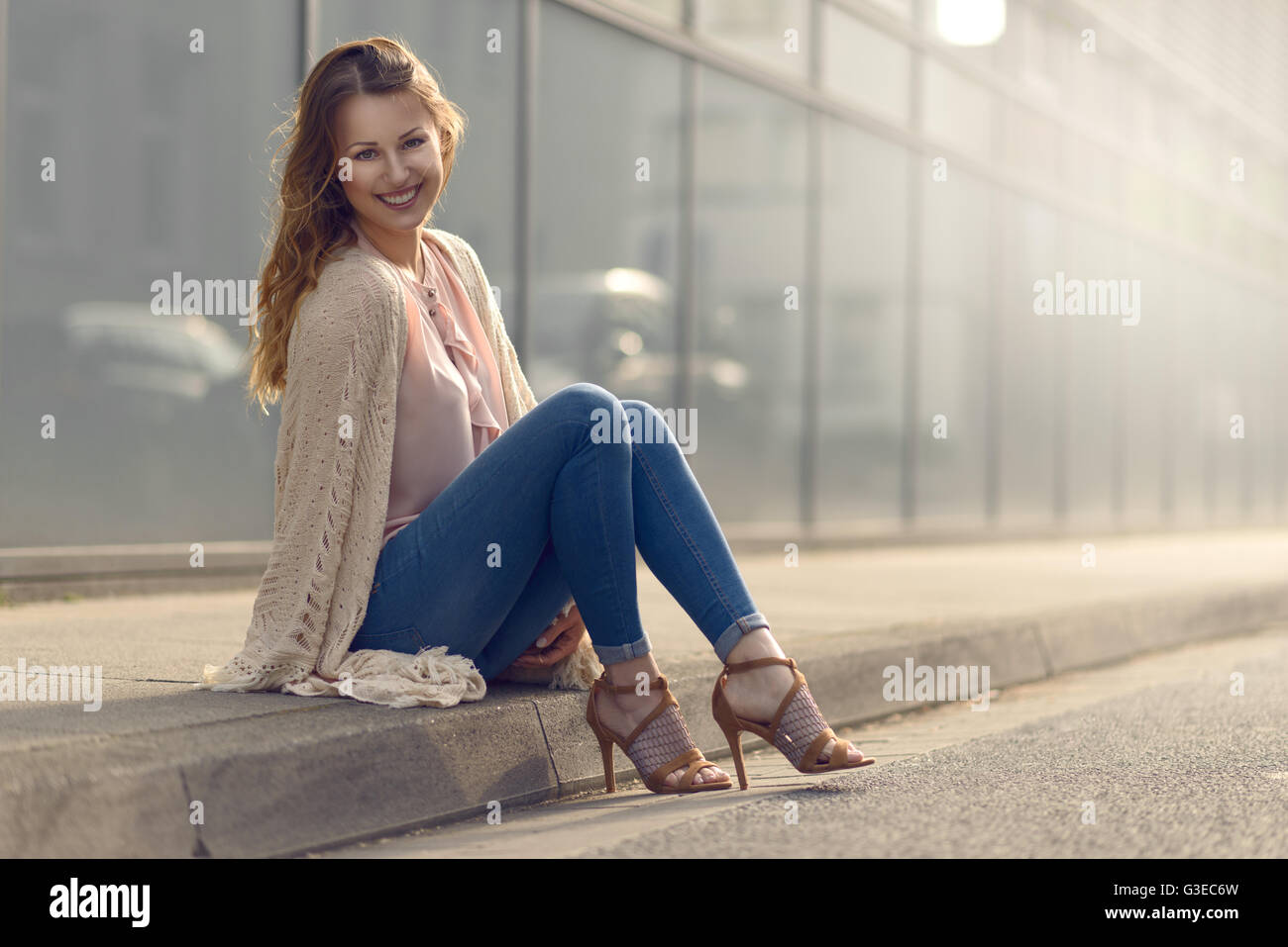 Smiling pretty trendy young woman sitting relaxing on a sidewalk on an urban street in her high heels and fashionable - Stock Image