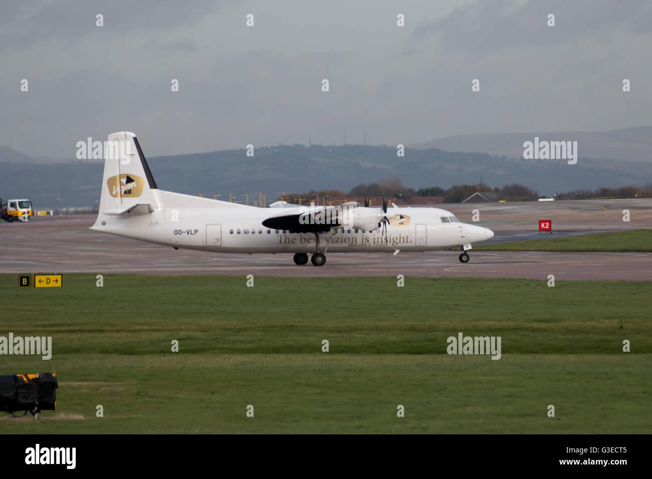 VLM Airlines Fokker 50 regional turbo-prop aircraft (OO-VLP) taxiing on  Manchester International Airport tarmac.