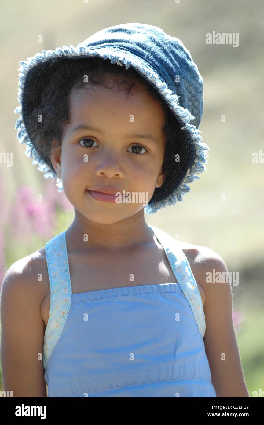 40a429c91f9 Mixed race young girl with denim hat and blue pinafore dress Stock ...