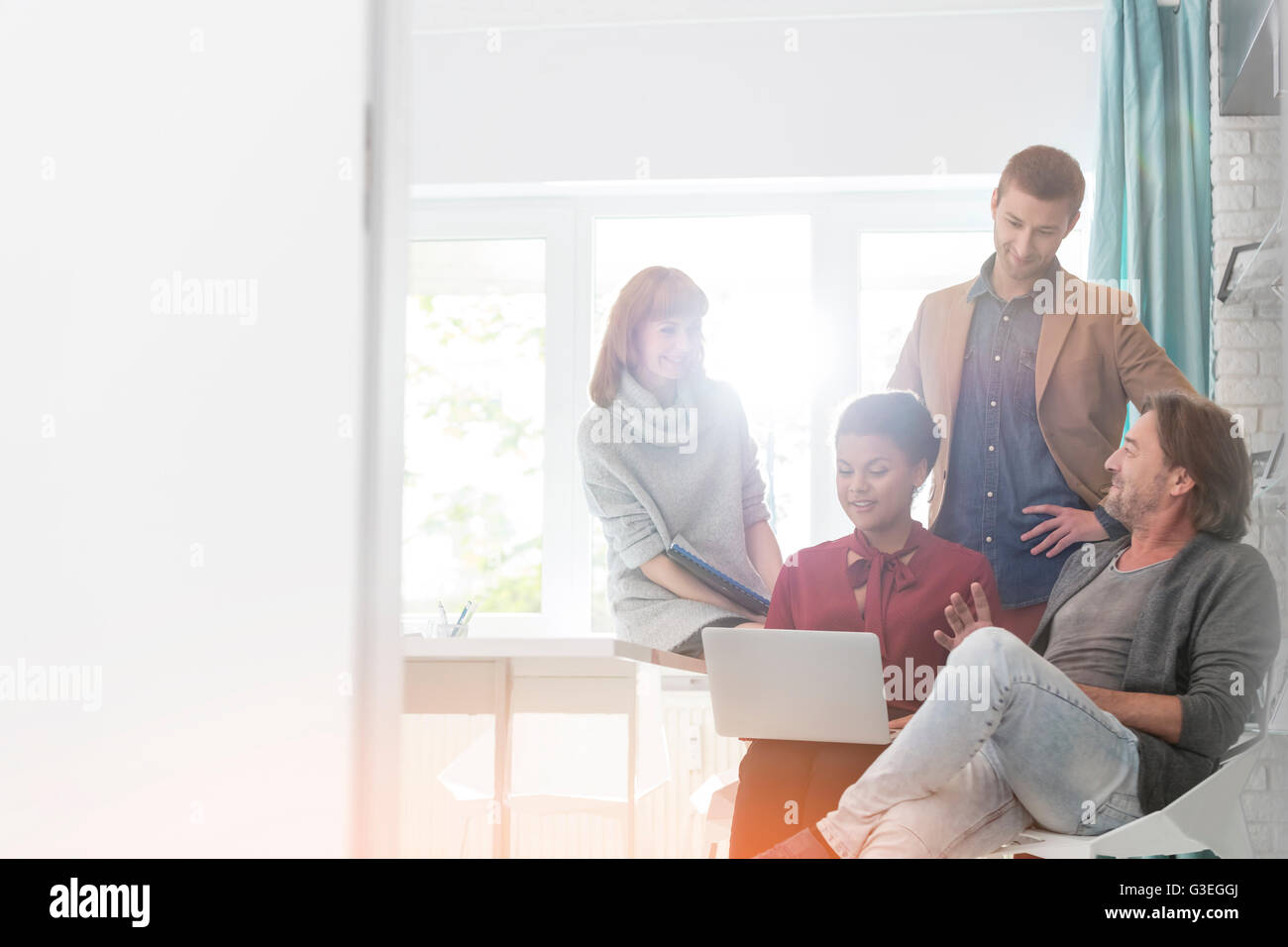 Creative business people using laptop in meeting - Stock Image