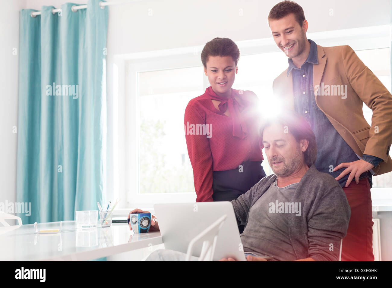 Business people sharing laptop in office meeting - Stock Image