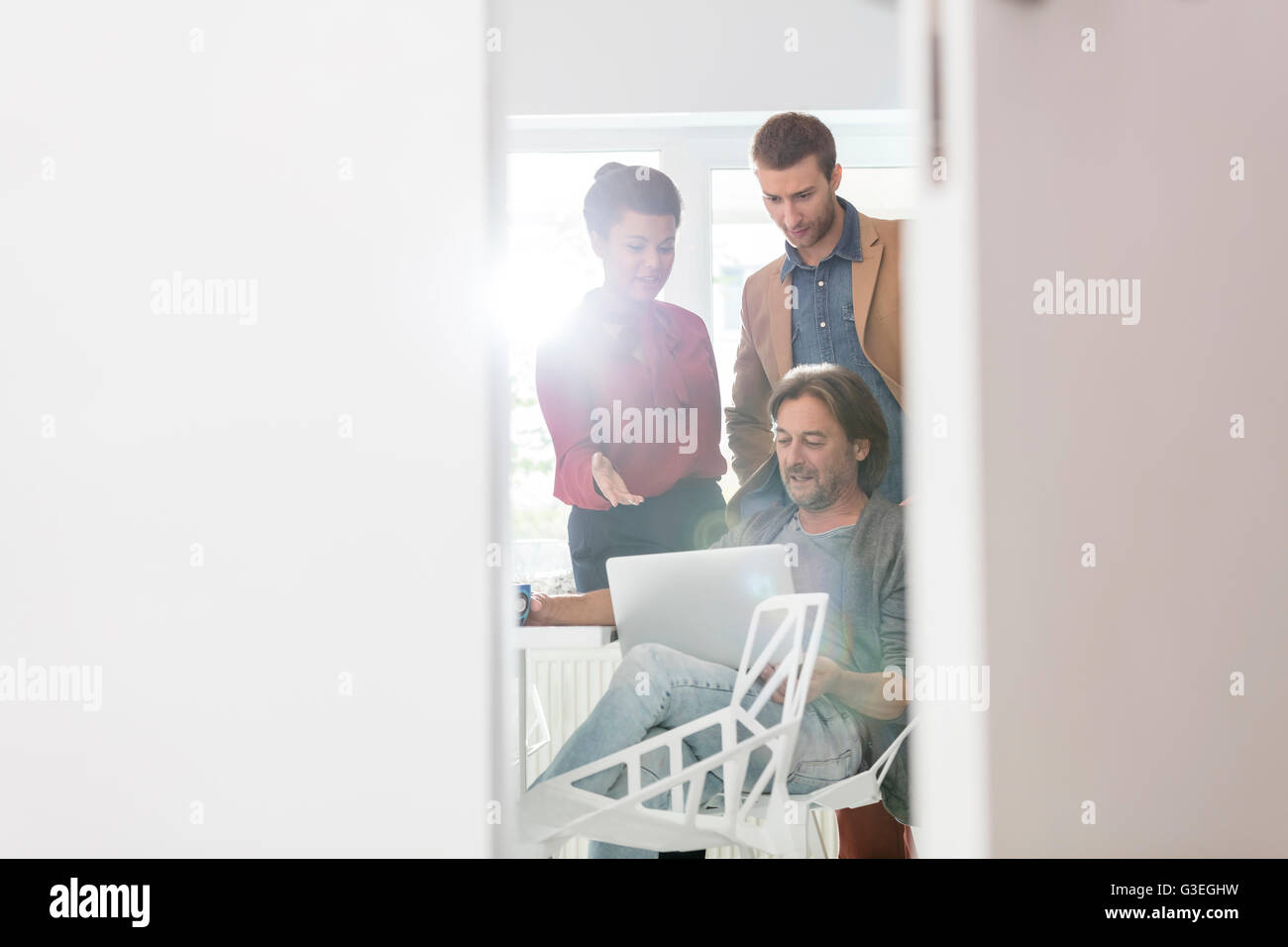 Creative business people sharing laptop in office meeting - Stock Image