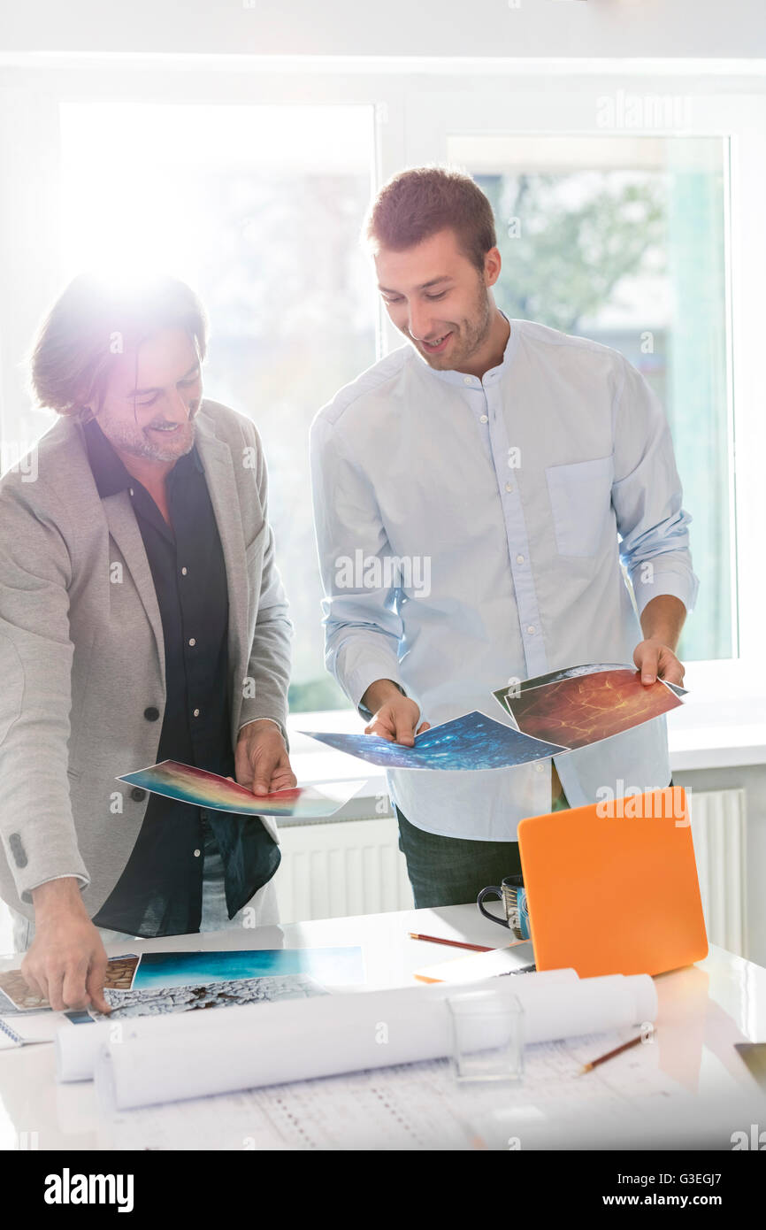 Creative businessmen reviewing photography proofs in office - Stock Image