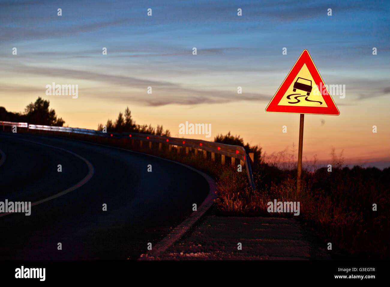 Curvy road sliding danger traffic sign at sunset next to road lane - Stock Image