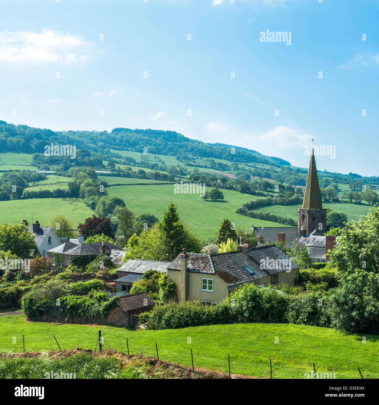 A small village and church spire in arural valley on a summer day. - Stock Image