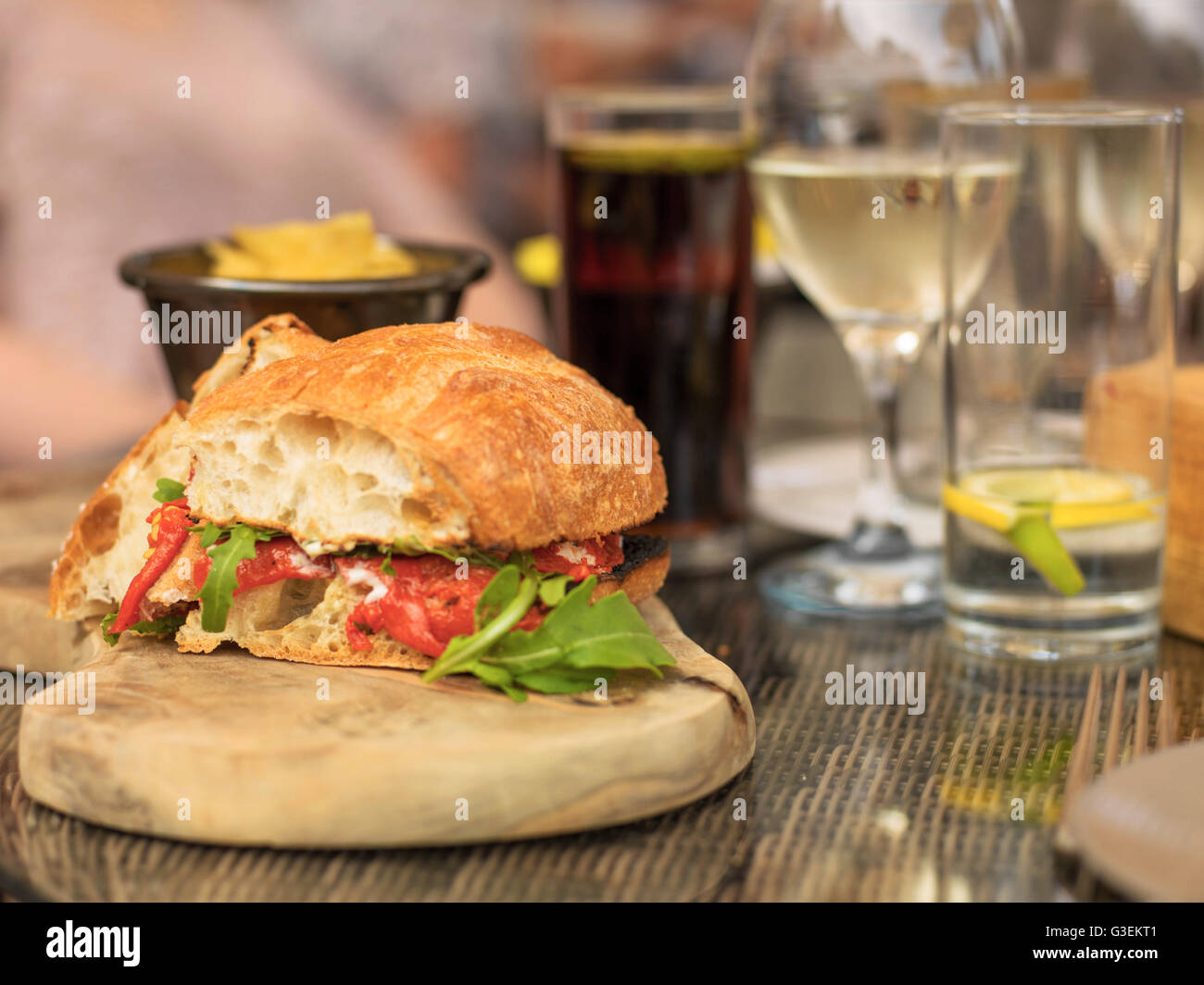 Vegetarian Red Pepper and Rocket Ciabatta Bread Sandwich or Roll with a Glass of White Wine and Water Stock Photo