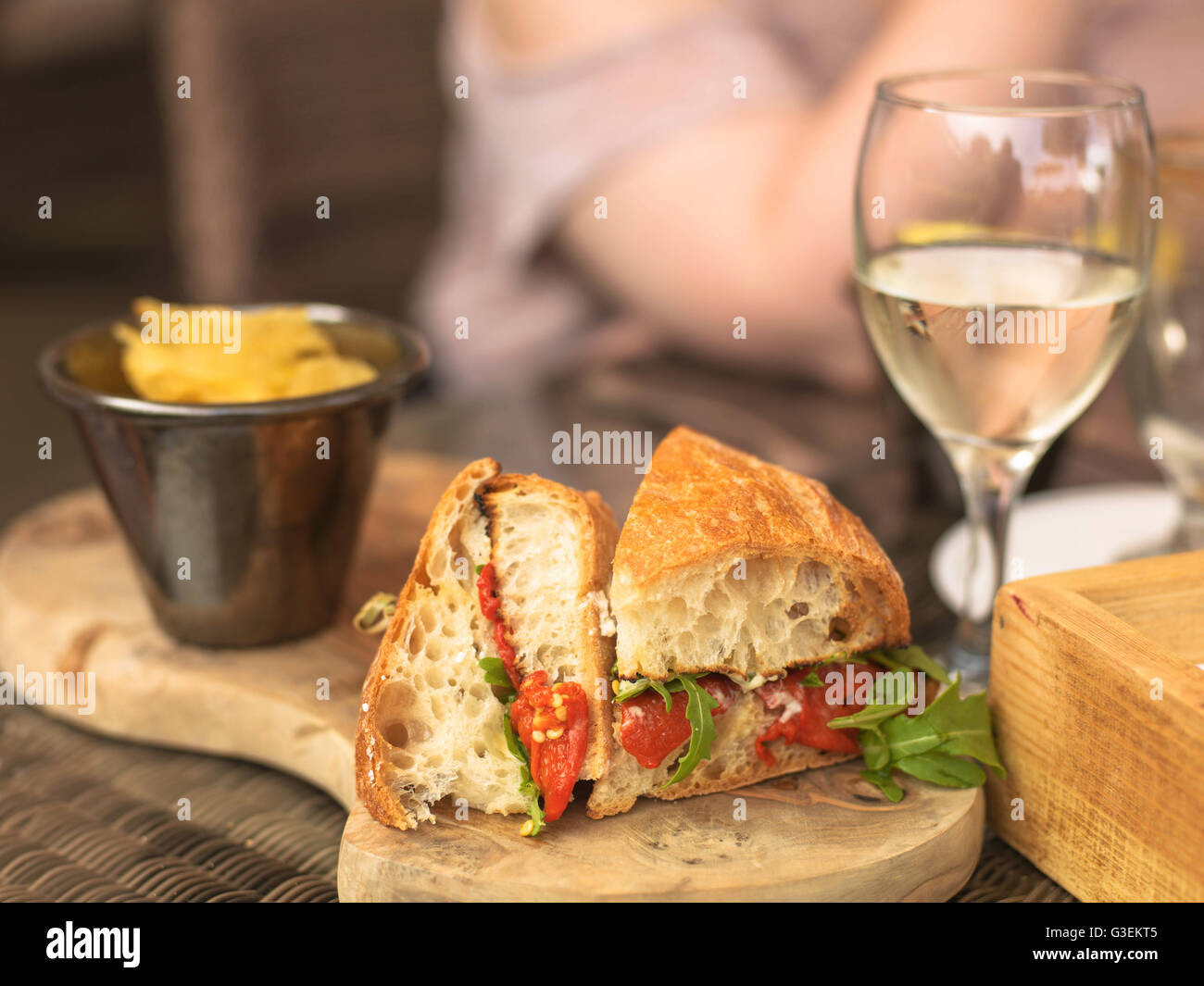Vegetarian Italian Style Red Pepper Ciabatta Bread Sandwich with a Glass of White Wine On a Wooden Serving Board Stock Photo