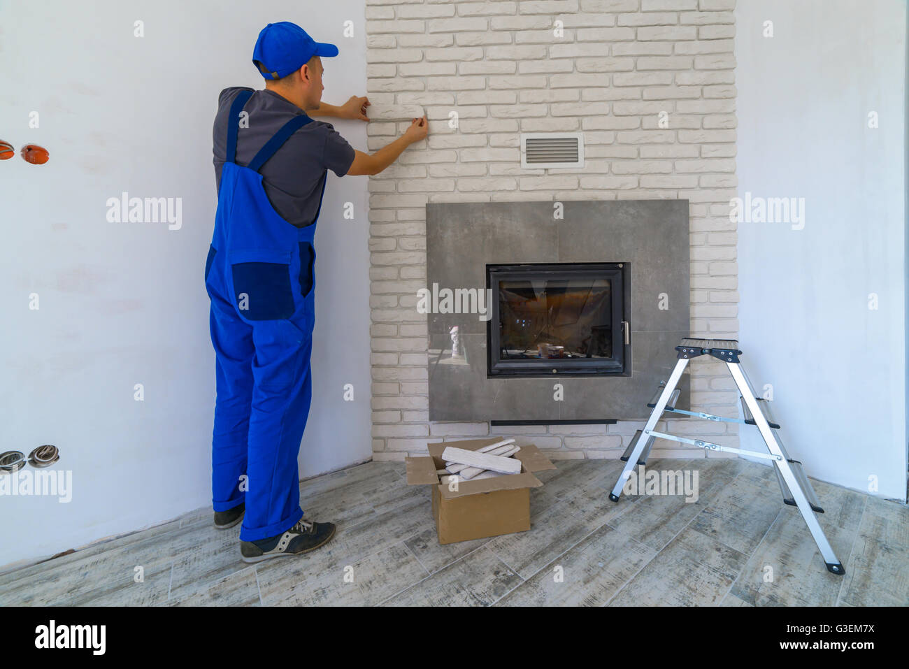 Fireplace installing in white brick wall - Stock Image
