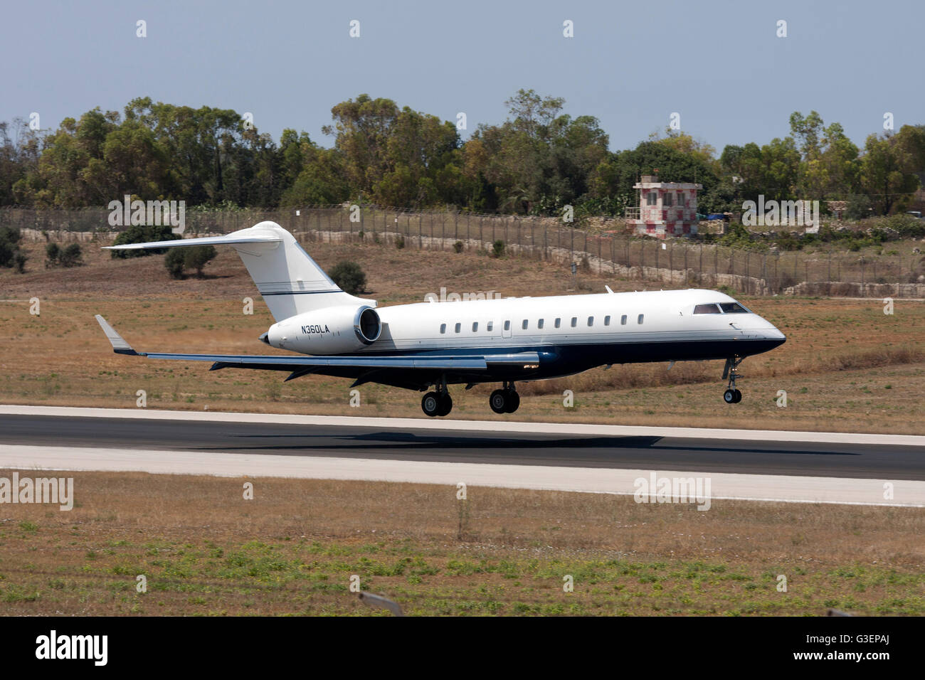 Bombardier BD-700-1A10 Global Express final moments before touch down on runway 32. - Stock Image