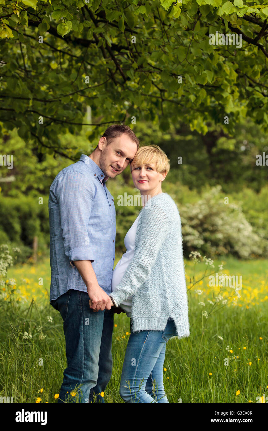 Happy couple in the park, pregnant woman and her husband - Stock Image