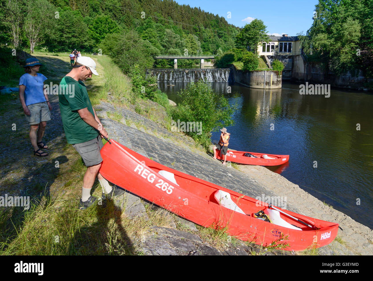 Paddler portage a canoe ( Canadian ) at hydroelectric power plant Gumpenried on the river Schwarzer Regen, Germany, - Stock Image