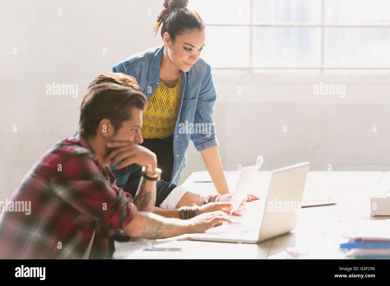 Creative young business people working at laptop in sunny office - Stock Image