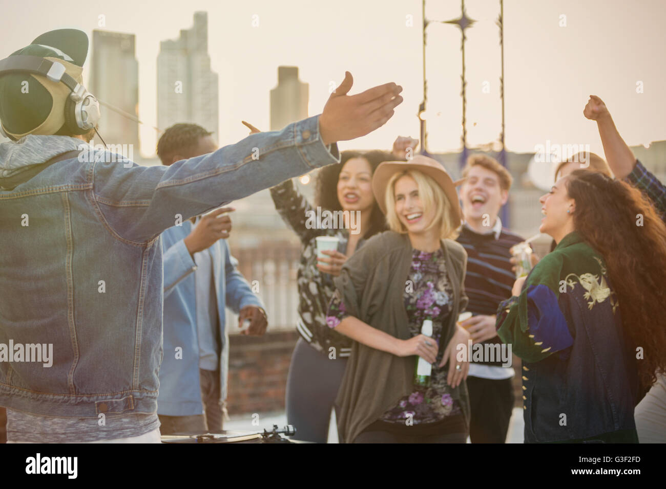 Crowd cheering for DJ at rooftop party - Stock Image