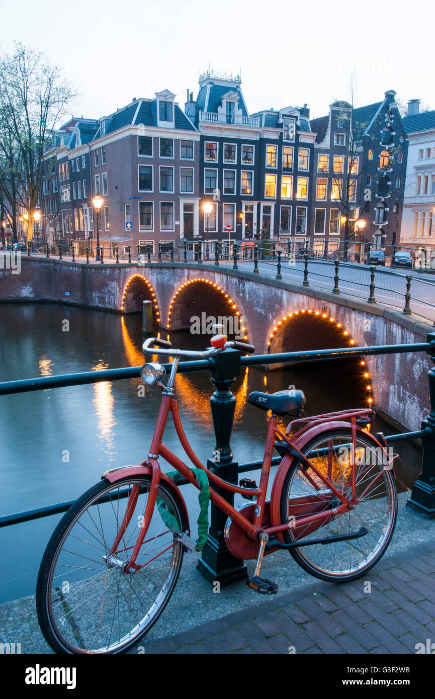 Bicycle at the handrail, dusk, 'Leidsegracht', corner 'Keizersgracht', Amsterdam, Holland, Netherlands - Stock Image