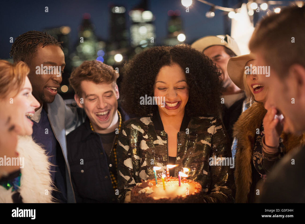 Friends celebrating young woman's birthday with cake and candles Stock Photo