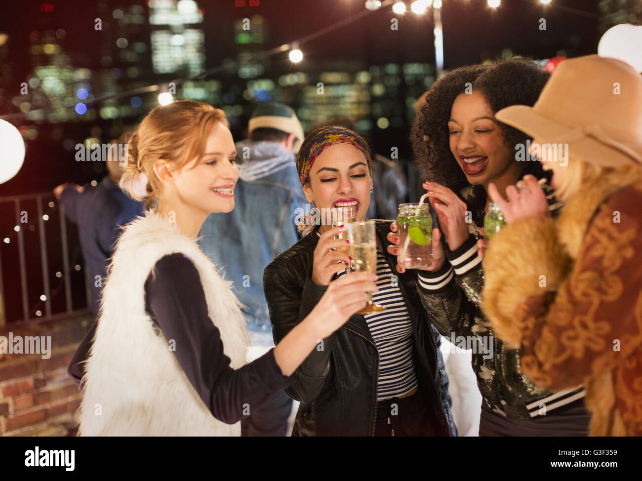 Young women drinking and enjoying rooftop party - Stock Image