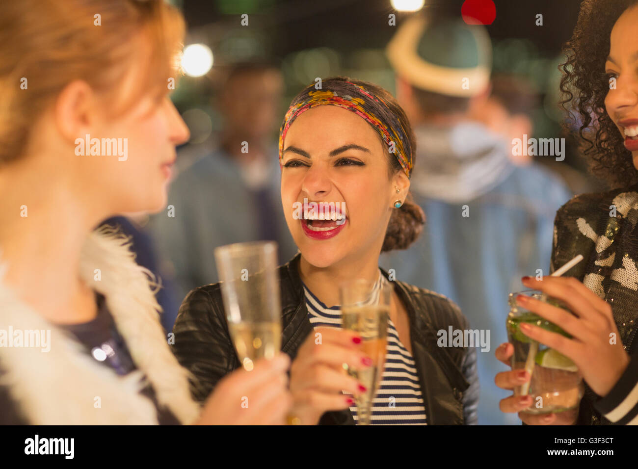 Enthusiastic young women drinking champagne and laughing at party - Stock Image