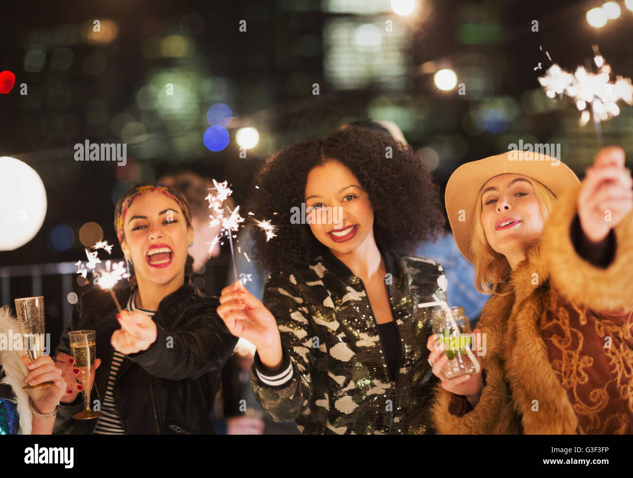 Portrait enthusiastic young women waving sparklers at party - Stock Image