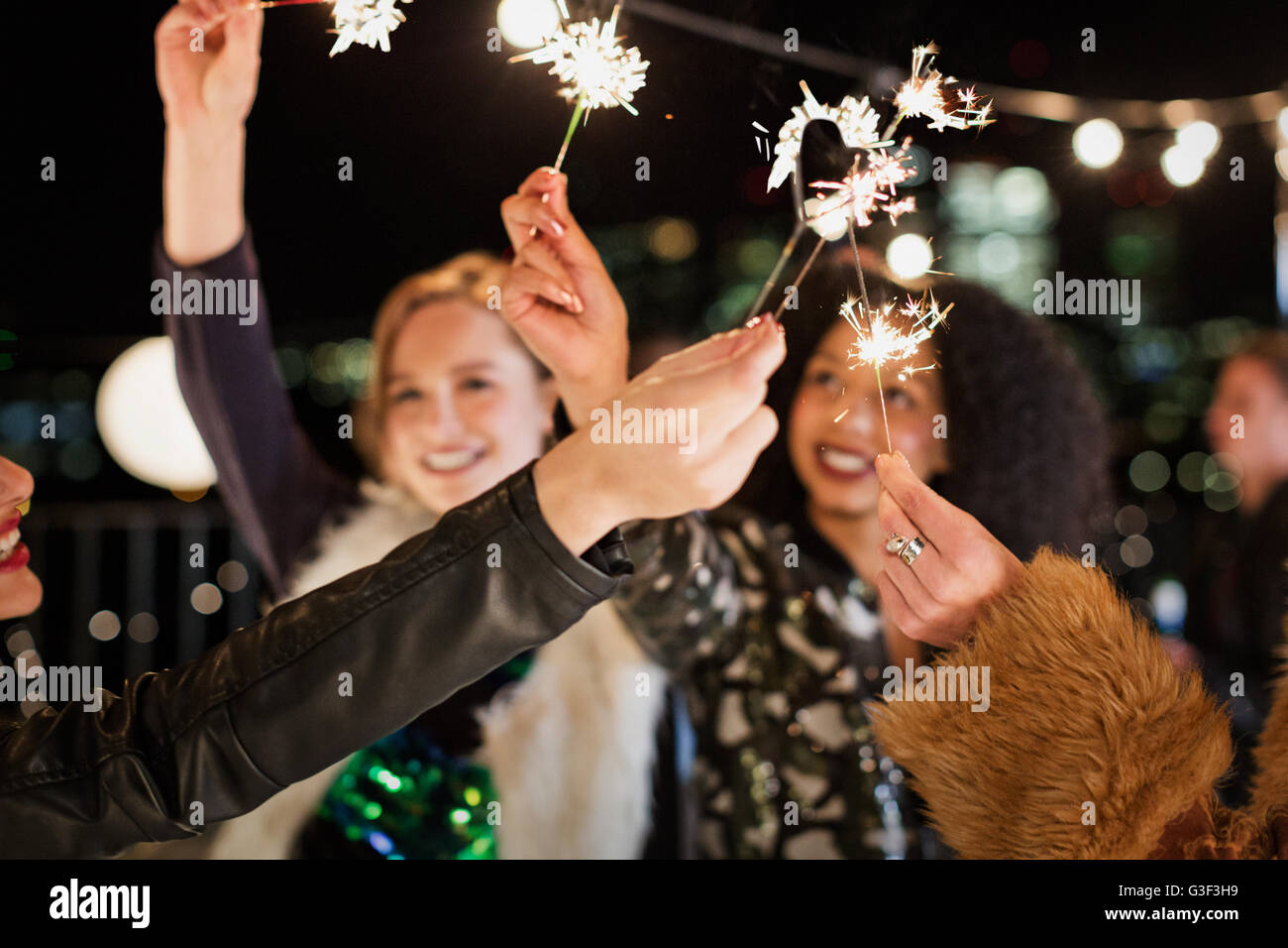 Young women waving sparklers at rooftop party Stock Photo