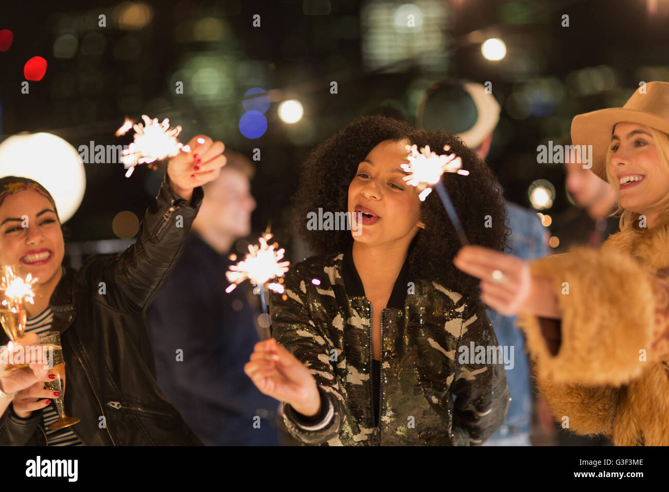 Young women waving sparklers at rooftop party - Stock Image