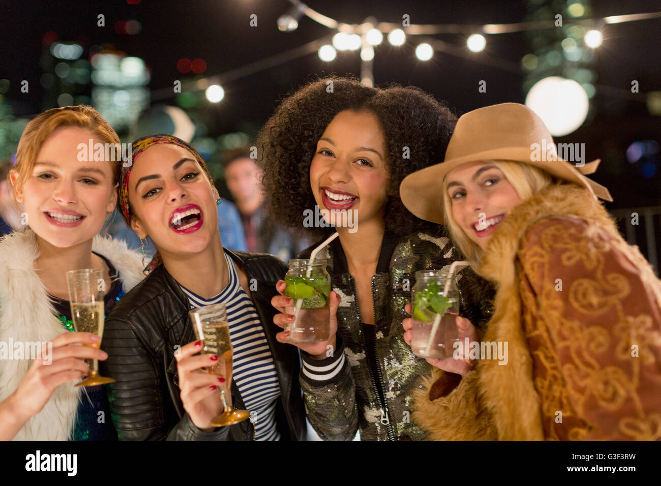 Portrait enthusiastic young women drinking cocktails at party - Stock Image