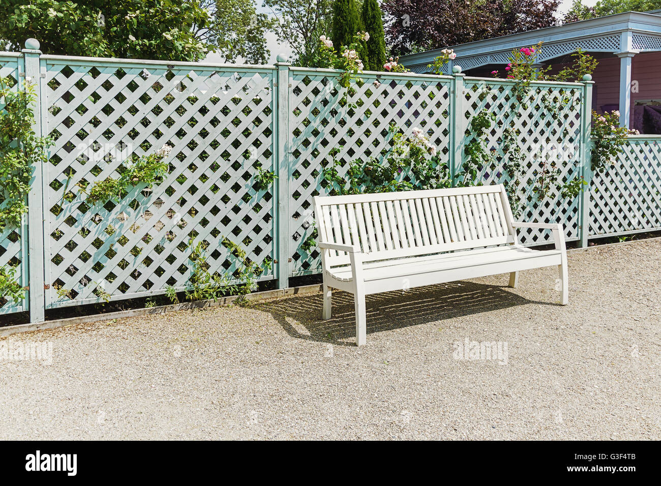 White openwork bench at the fence in the park. - Stock Image