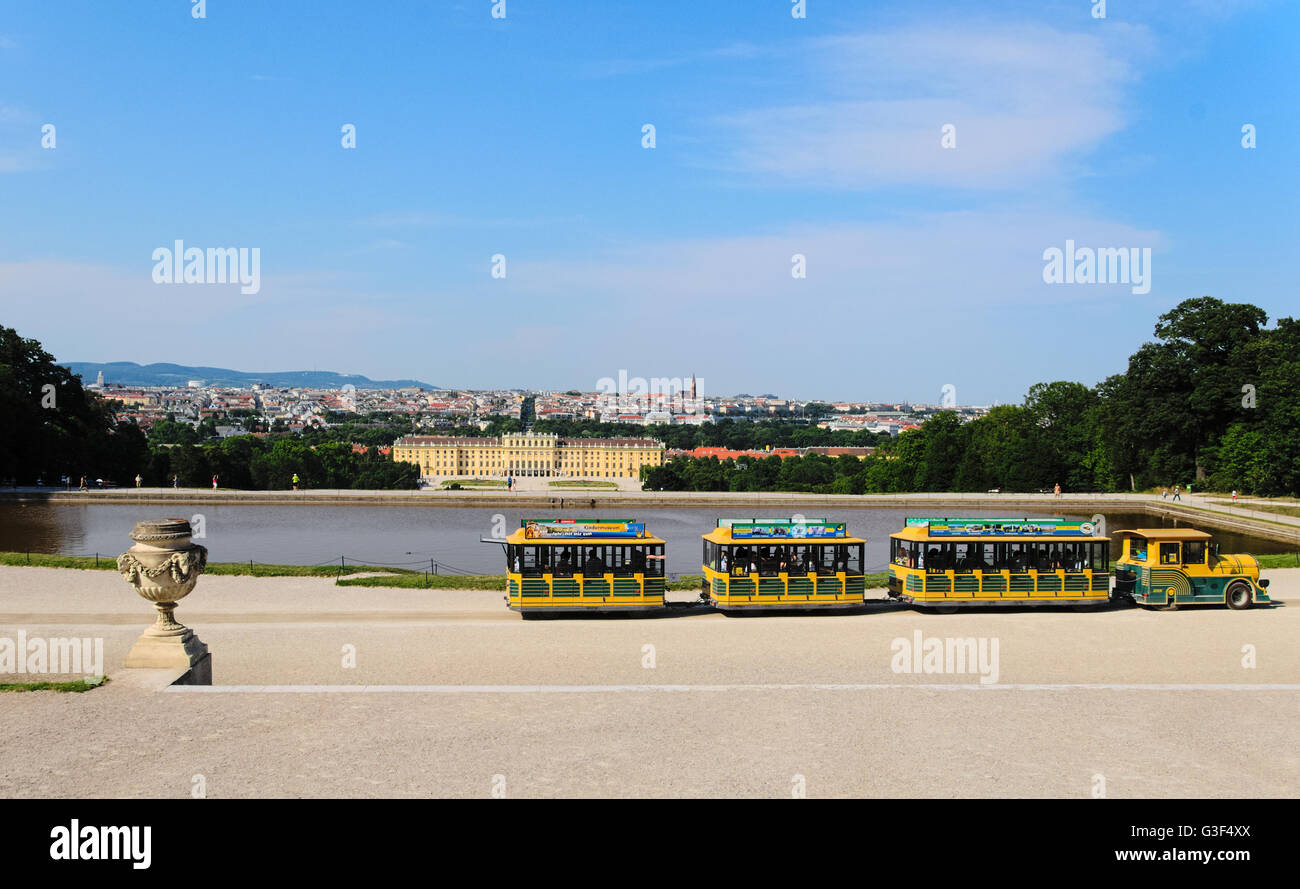 Panoramic view of the Schonbrunn Palace in Vienna with the touristic small train in the foreground - Stock Image