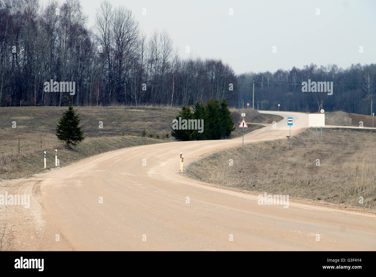 Twisting winding meandering gravel road in meadow with signs near forest - Stock Image