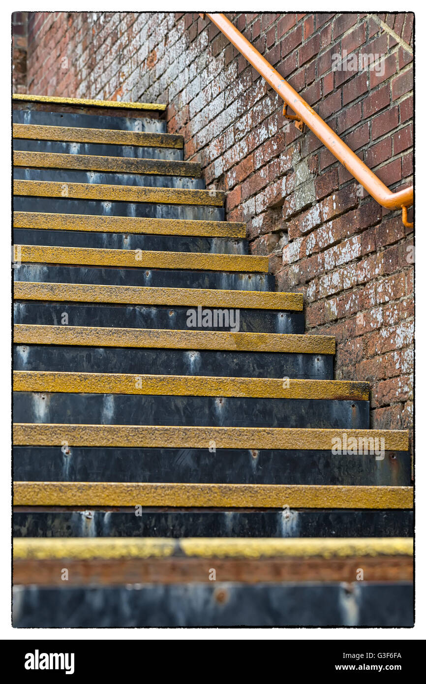 Detail of flight of stairs with yellow coloured safety threads and orange coloured stainless steel handrail, in - Stock Image