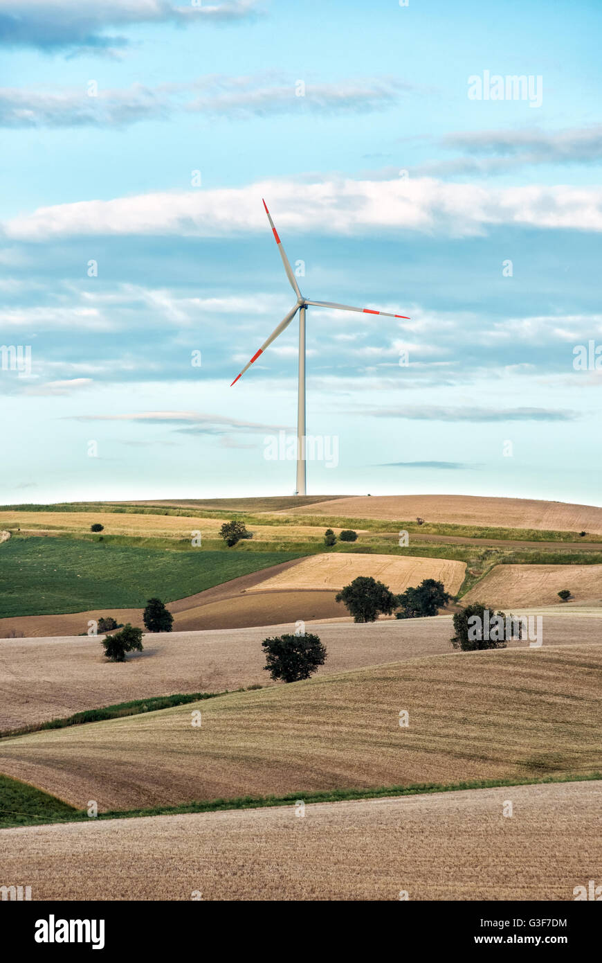 Rolling agricultural hills with a single wind turbine in the distance on the horizon providing renewable electricity - Stock Image