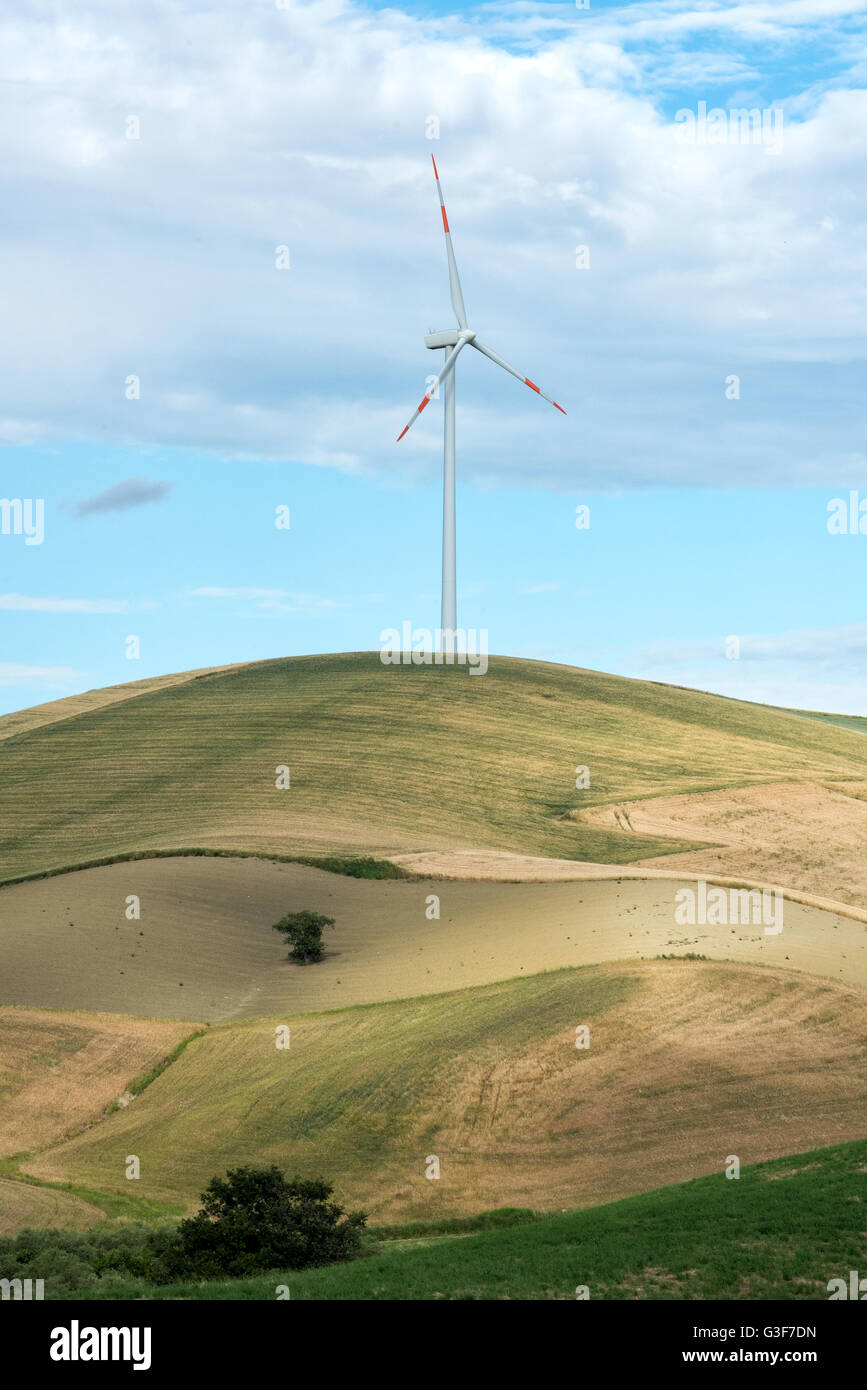 Single wind turbine in farmland on a hilltop with rolling fields and meadows providing a source of renewable electricity - Stock Image