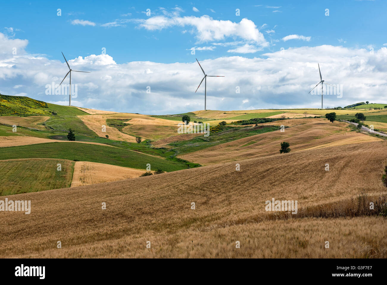 Row of wind turbines in a wind farm on the hilltops viewed across rolling agricultural land in a concept of alternative - Stock Image