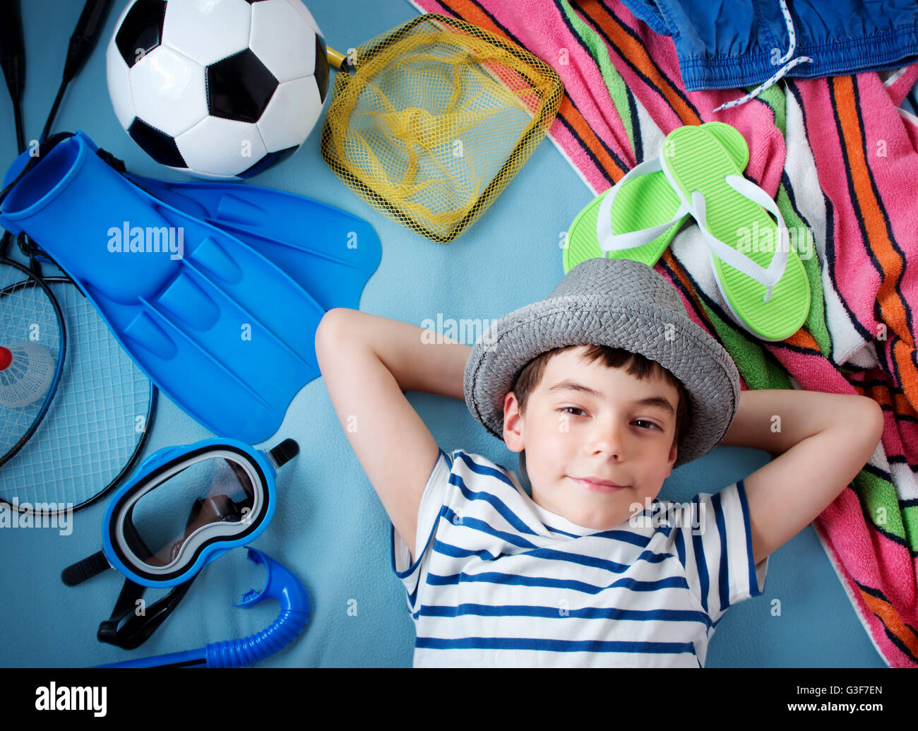 boy in straw hat with towel and toys Stock Photo