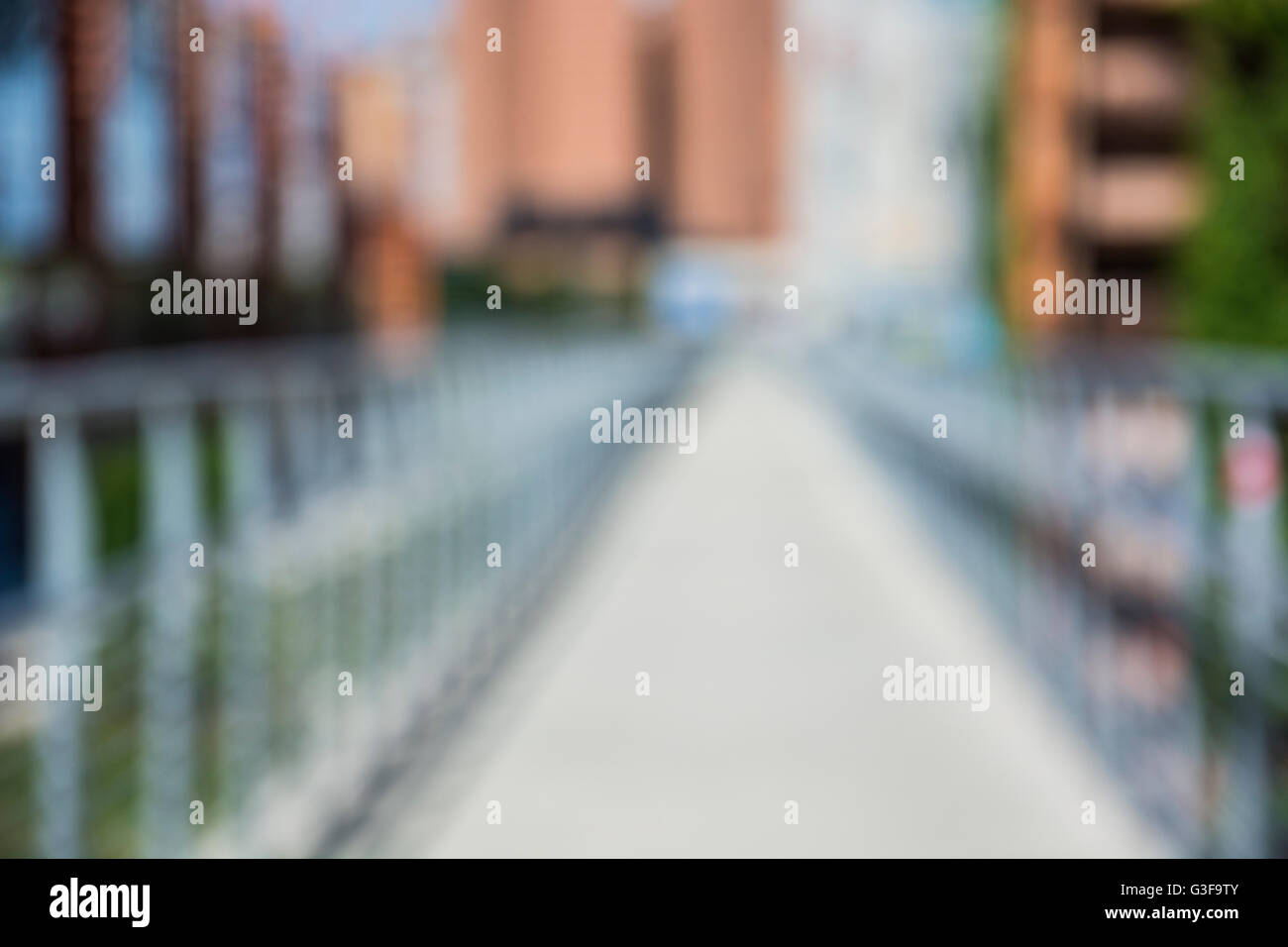 Unfocused blurred view on bridge and summer alley, in city setting. Urban environment background - Stock Image