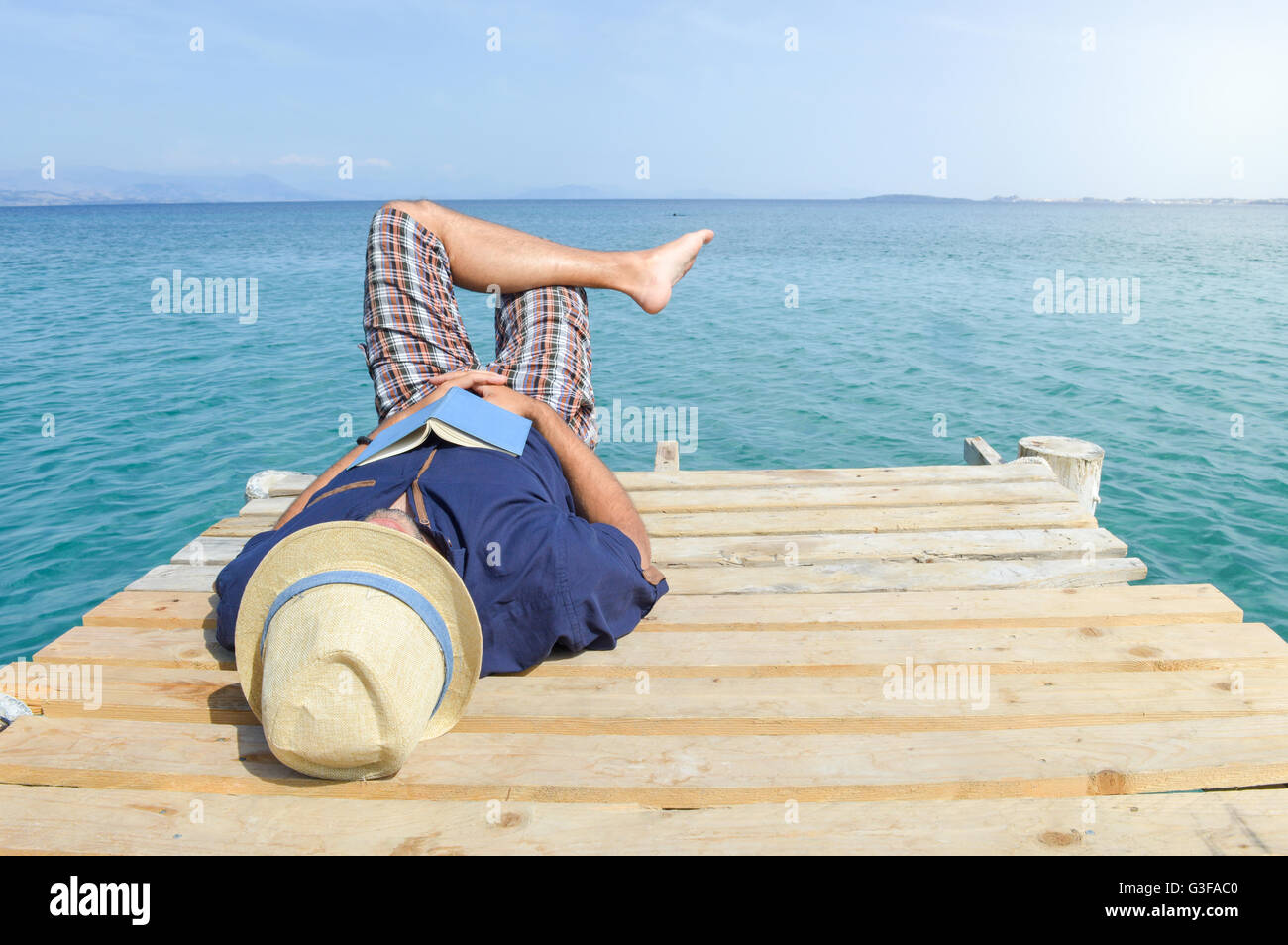 Man lying on the dock with a book. Summer vacation relaxation - Stock Image