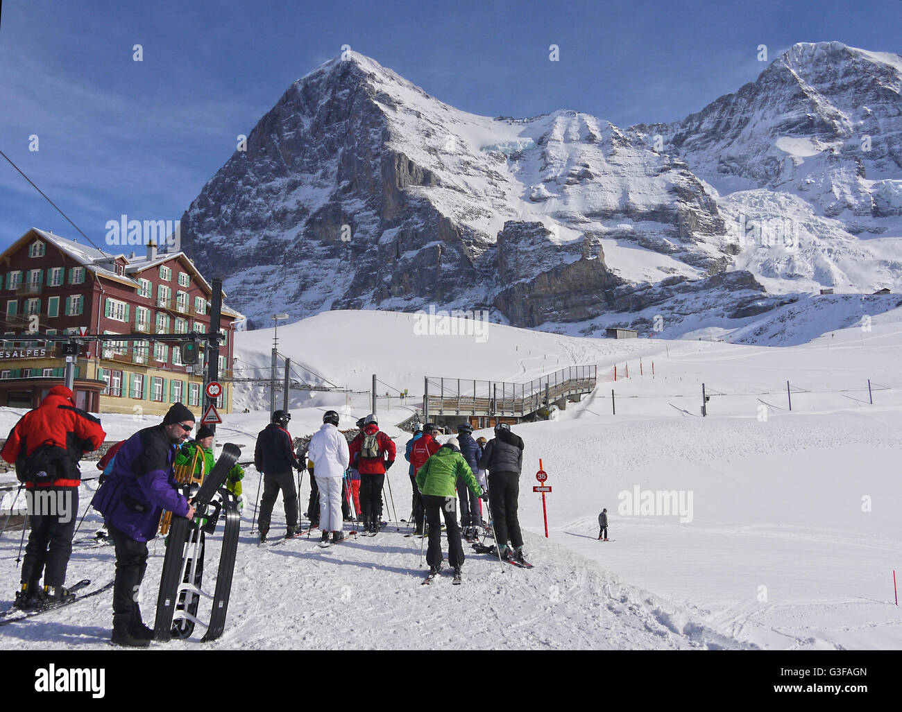 Skiers and snowboarders at Kleine Scheidegg station with the Eiger mountain behind - Stock Image
