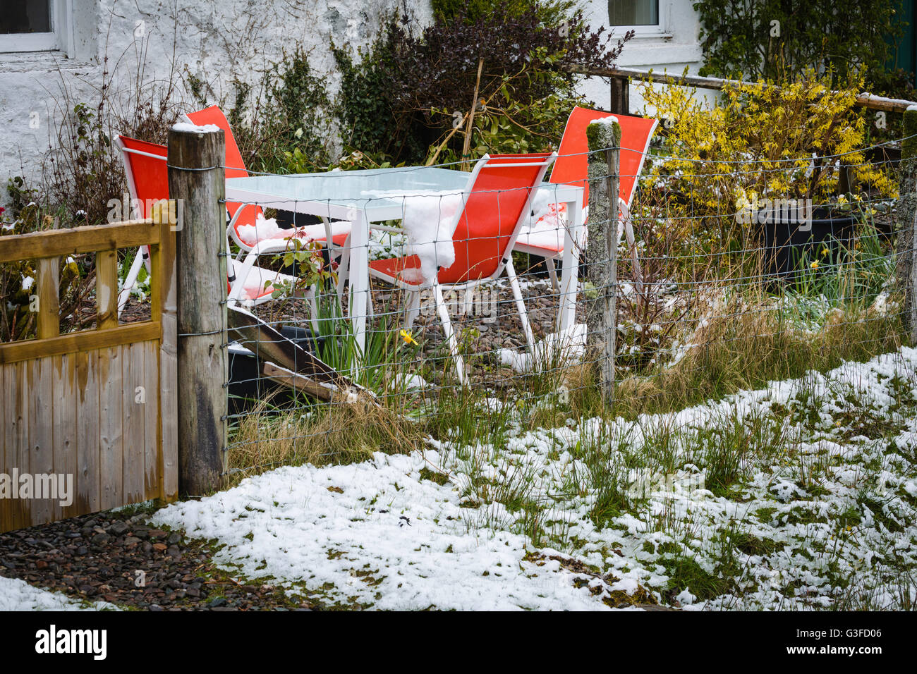 Garden furniture left outside after unseasonal snow fall. - Stock Image