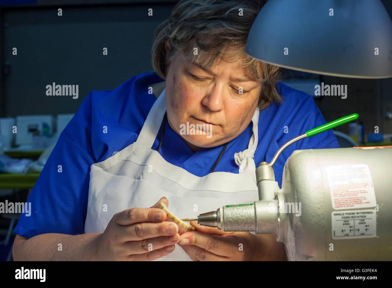Warren, Michigan, USA. 10th June, 2016. A dental technician repairs a denture during a free, two-day dental clinic - Stock Image