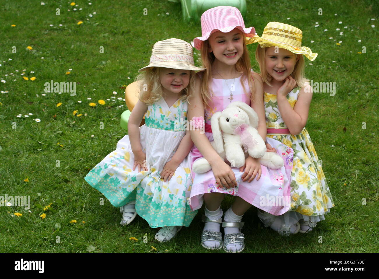 Three sisters, children sitting in the garden at Easter wearing easter dresses and easter bonnets - Stock Image