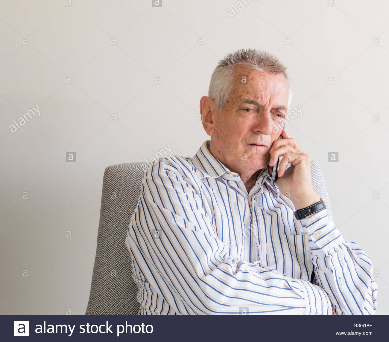 Older man in striped shirt talking on mobile phone and looking concerned - Stock Image