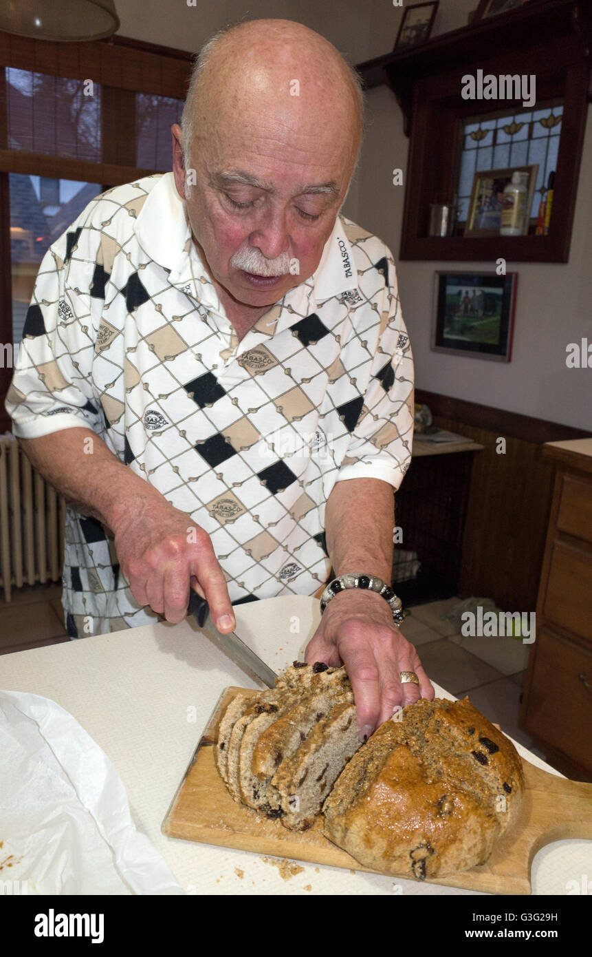 Man age 70 slicing a loaf of traditional soda bread at St Patrick's Day festivities. St Paul Minnesota MN USA - Stock Image
