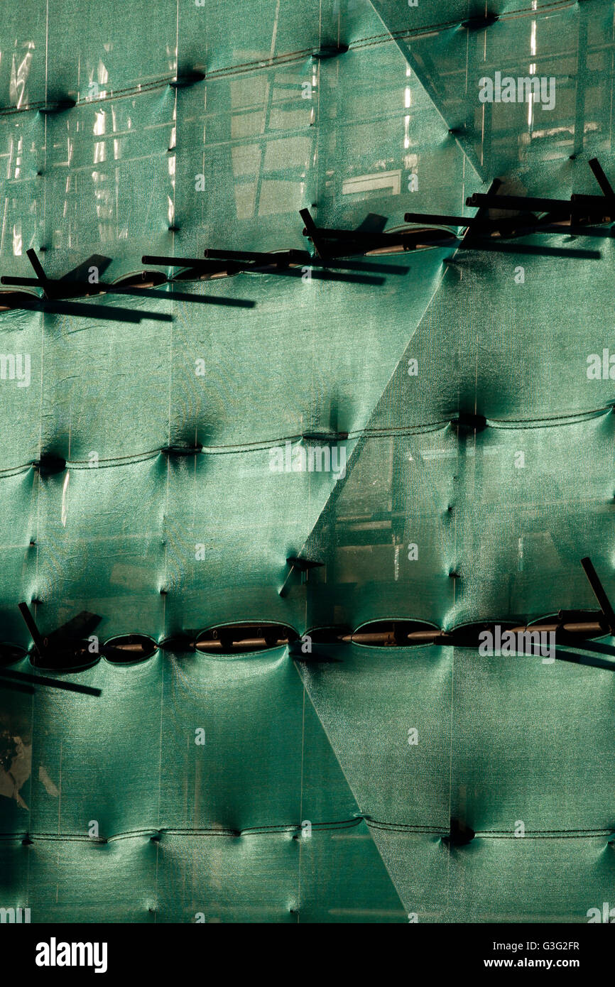 New building construction with scaffolding and green dust sheet netting - Stock Image