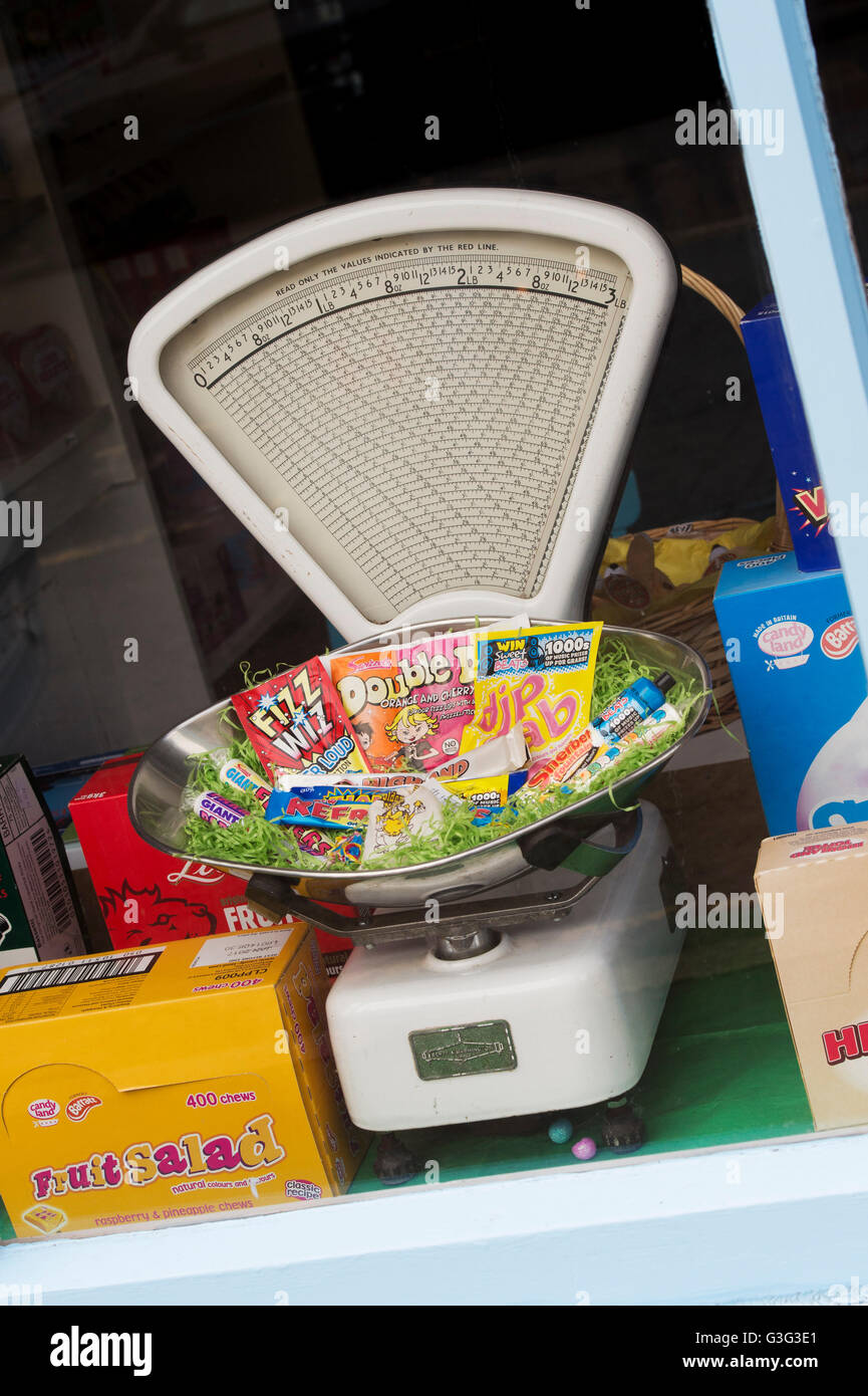 Old vintage weighing scales and childrens sweets in a sweet shop window. Tetbury. Cotswolds, Gloucestershire, England Stock Photo