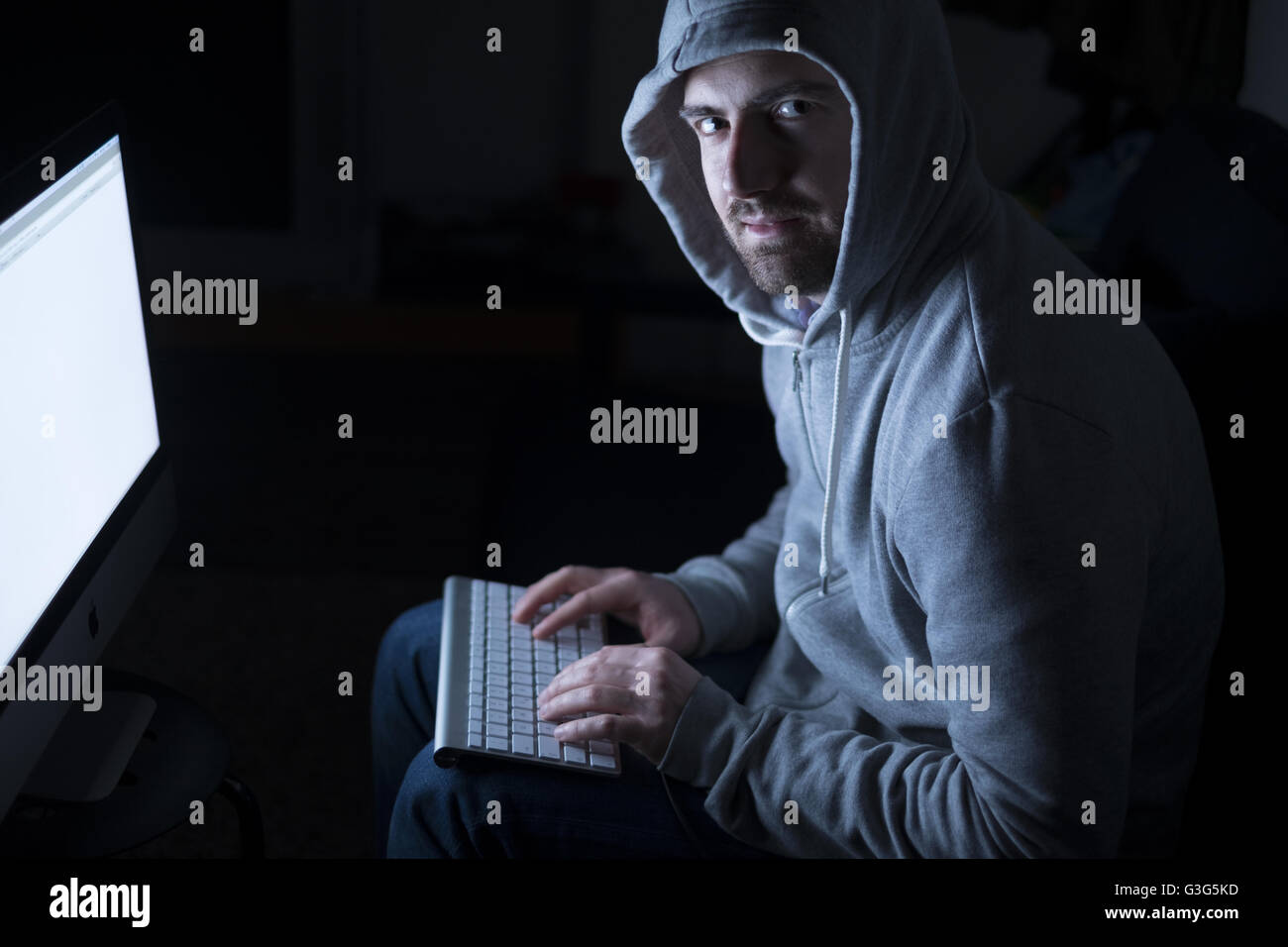 Portrait of hacker in the sitting in front of computer with glow - Stock Image