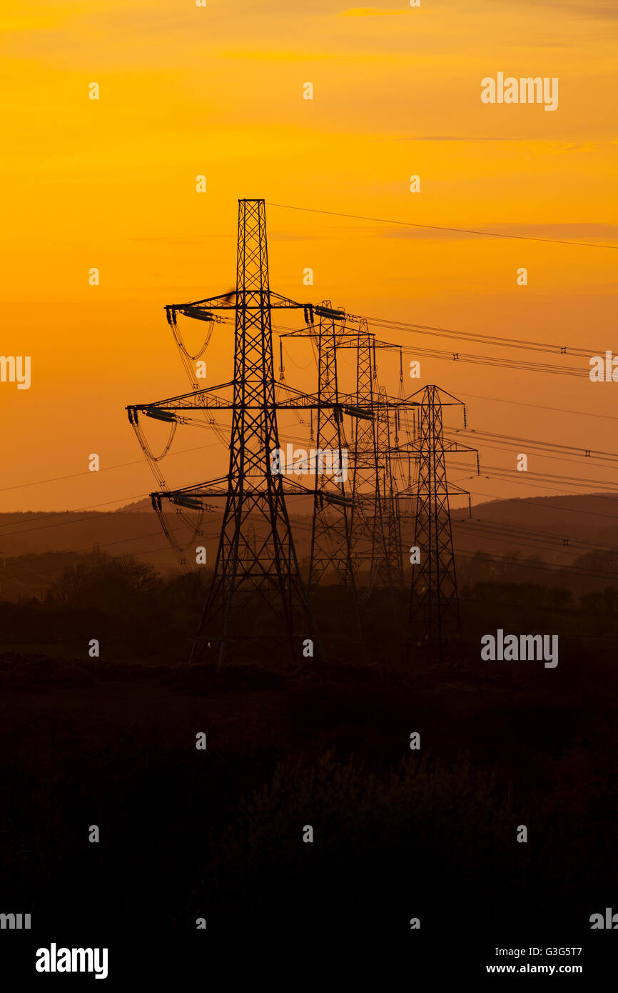Silhouetted powerlines or pylons on Halkyn Mountain transporting electrical energy over North Wales, UK - Stock Image