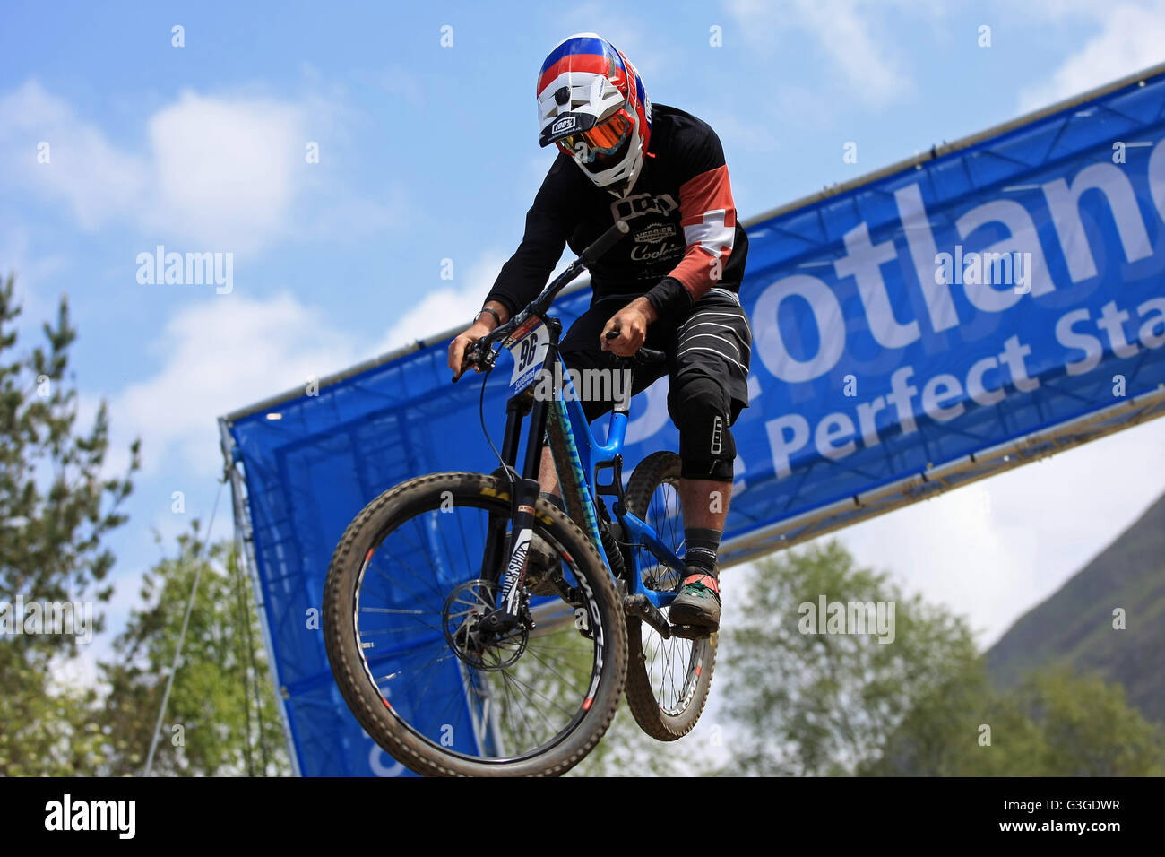 Maxime Chapuis SUI with seat grab jumping through the Scotland Arch at the Downhill Mountain Bike World Cup at Fort - Stock Image