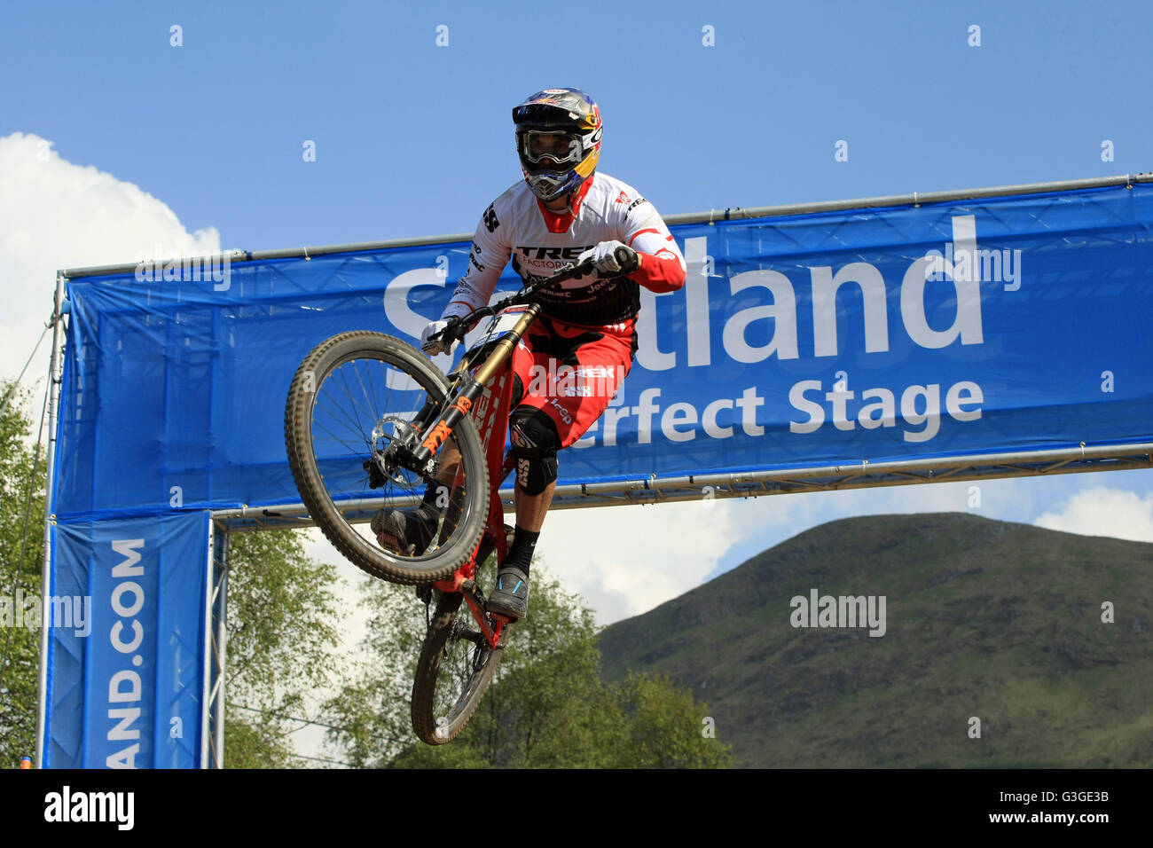 Gee Atherton jumping through the Scotland Arch at the Downhill Mountain Bike World Cup at Fort William, Scotland - Stock Image