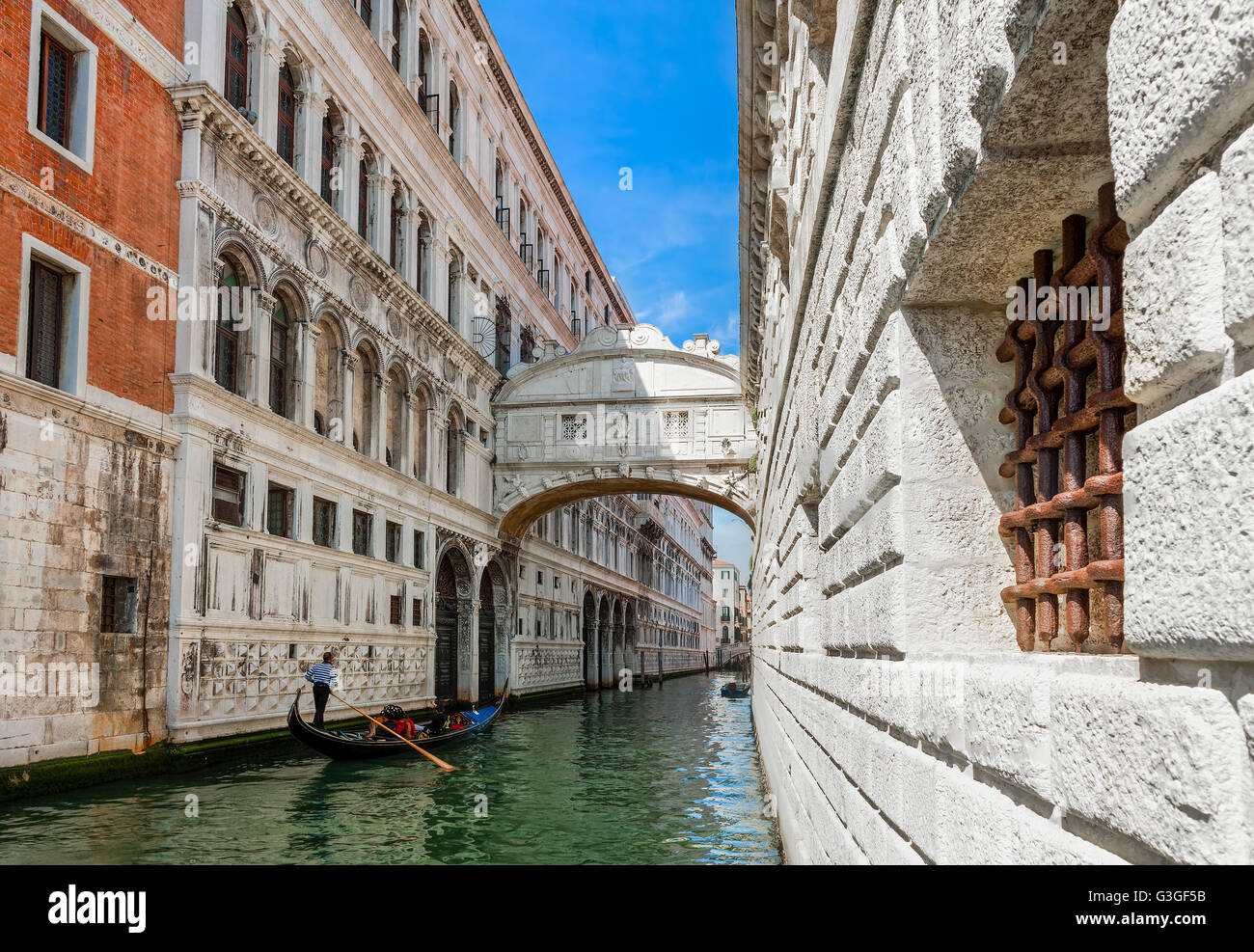 Gondola passing on narrow canal under famous Bridge of Sighs in Venice, Italy. - Stock Image