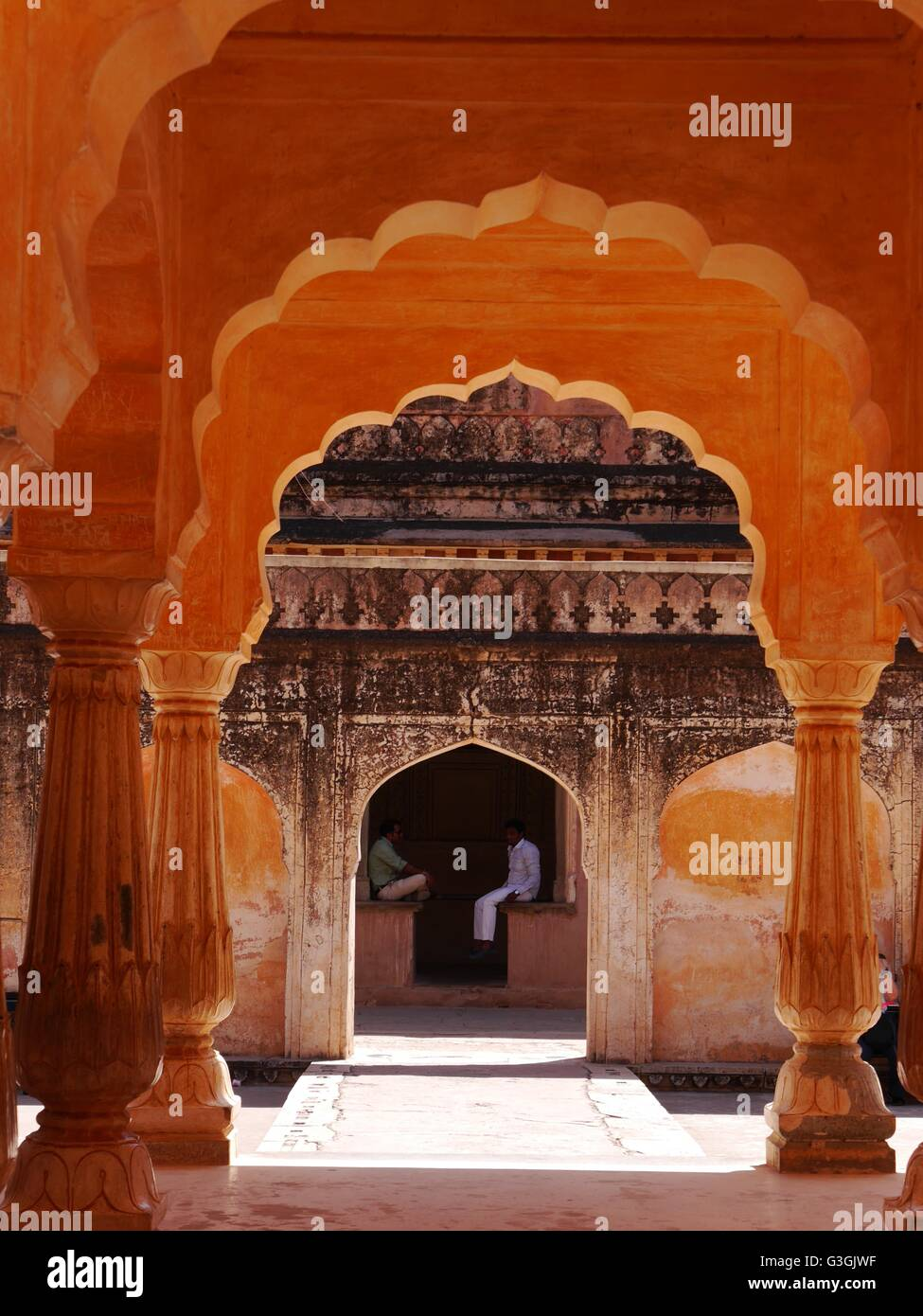 Picturesque view through successive amber archways of two men talking in the City Palace (Chandra Mahal) Jaipur - Stock Image