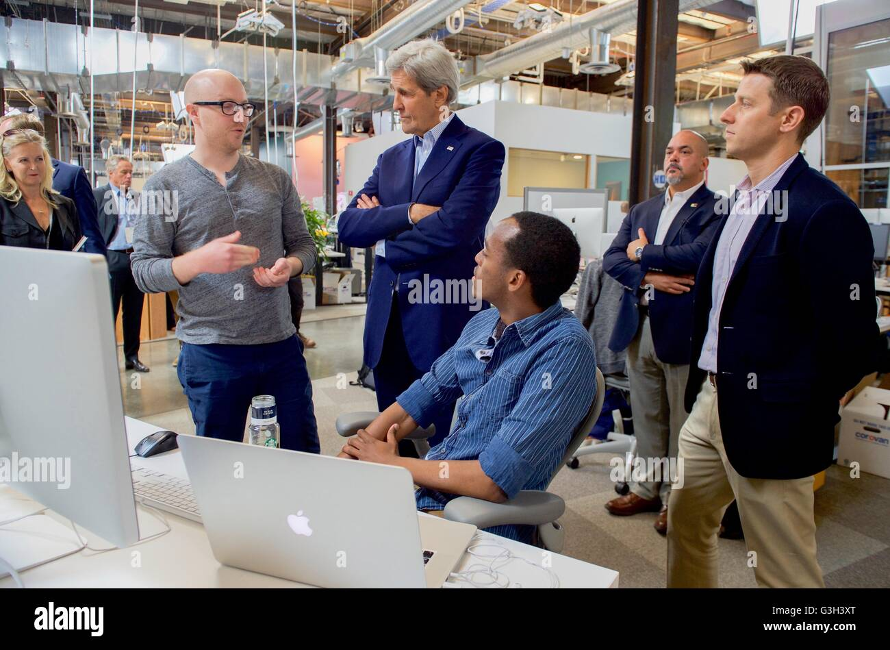 U.S. Secretary of State John Kerry chats with software developers before meeting with CEO Mark Zuckerberg at Facebook's - Stock Image